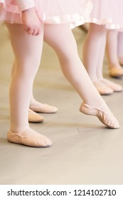 Baby ballet feet pointed in a pink skirt