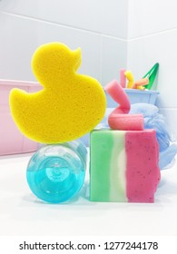 Baby bath items in bathroom. Yellow washcloth-duck, colourful baby soap and shampoo for baby bathing