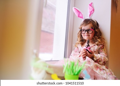 baby beautiful girl in a smart dress with rabbit ears on her head holding a chocolate Easter bunny sitting on a window sill against a window.