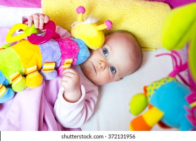baby in bed with a colorful toy