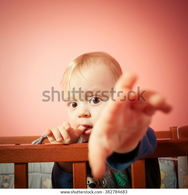 Baby in bed pulls the plug on pink background