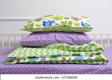 Baby bedding on the bed, pillows and blanket.