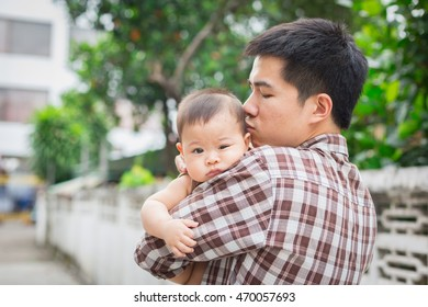 baby is being carried by father. father always carries him because he loves his son.