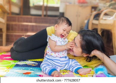 baby is being carried by mother.mother loves her daughter.she is always happy when they play together.