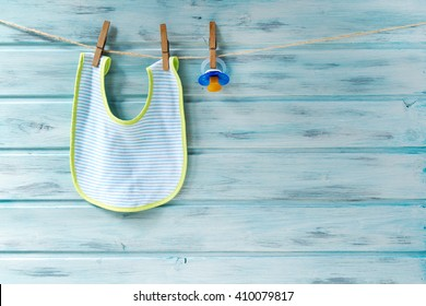 Baby bib and pacifier hanging on a clothesline on wooden background