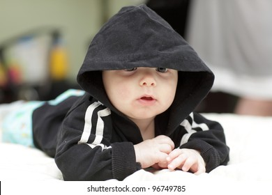 The baby in a black suit with hood at home