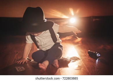 A baby in a black wide-brimmed hat sits in a room next to the playing cards scattered on the floor and the flashlight on
