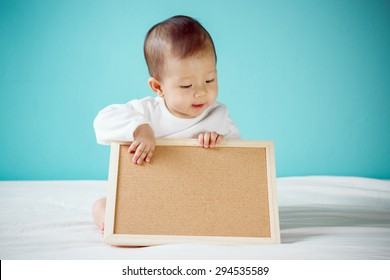 Baby with Blank Board copy space and sitting on the bed in the blue room, Baby healthy and preschool concept