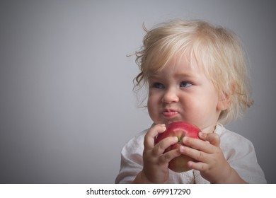 baby with blond long hair holds a red apple  eating
