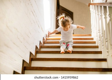 Baby blonde girl in white t-shirt at bottom of stairs indoors