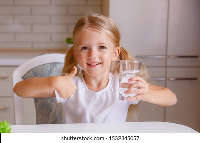 baby blonde shows thumbs up with a glass of water in her hand. Child girl holding a glass of water. Child recommend drinking water. Good healthy habit for children. Healthcare concept