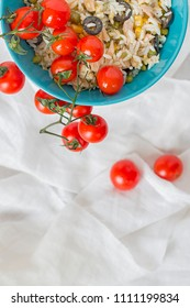 A baby blue bowl with cold rice salad with tomatoes hanging.