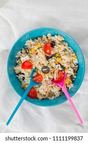 A baby blue bowl with cold rice salad with two spoons.