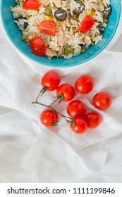 A baby blue bowl with cold rice salad and tomatoes.