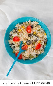 A baby blue bowl with cold rice salad with a spoon