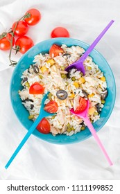 A baby blue bowl with cold rice salad with three spoons and tomatoes.