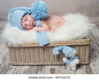 baby in blue hat sleeping on fluffy blanket in wicker basket
