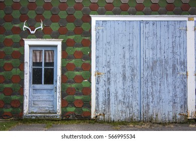 baby blue old doors of a green and red checkered farm wall