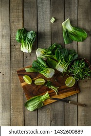Baby bok choy halves, lime wedges on a cutting board to demonstrate cooking process. Shot vertically on a rustic wooden background.
