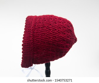 Baby bonnet knit berry color isolated on a light background.  This baby hat clothing related has a white satin ribbon to tie for infants.
