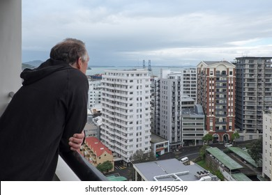 Baby boomer retired man looks at view of apartment buildings from balcony in Auckland, New Zealand, NZ