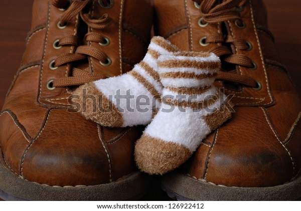 Baby booties nestled on top of parent's well worn leather shoes.  Macro with shallow dof.