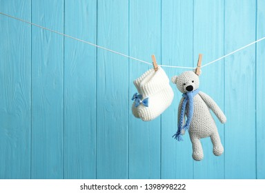 Baby booties and toy bear on laundry line against color wooden background, space for text. Child accessories