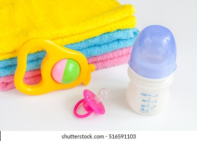 baby bottle with milk and towel on white background