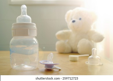 Baby bottle, pacifier and a baby's toy on a wooden table