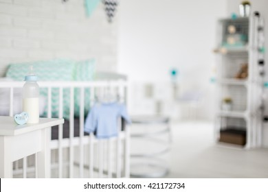 Baby bottle and pacifier in a blurred bright baby room