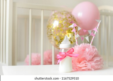 Baby bottles with breast milk with various festive paper decor and balloons in front of baby bedroom. It's a girl or baby birthday celebration concept. Baby shower concept.