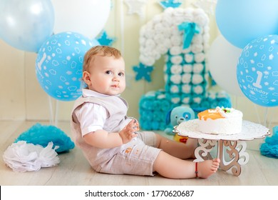 baby boy 1 year in a photo Studio with a cake and balloons, Birthday of a child 1 year, baby eats cake