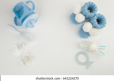 Baby boy accessories background: booties, tiny rod, soother, brush, and toys over white background with copy space; top view. Concept of Infancy and motherhood