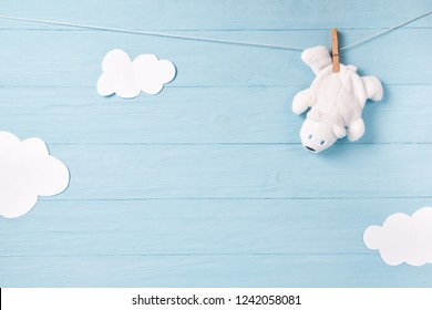 Baby boy background with white teddy bear toy on a clothesline and clouds