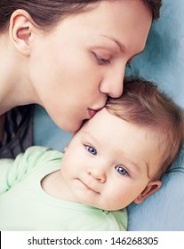 Baby boy with beautiful blue eyes being kissed by his mother.