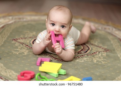 The baby boy biting a alphabet on a carpet at home