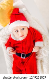 7f427565d baby boy with blue eyes in a Santa Claus costume lying on a blanket and a