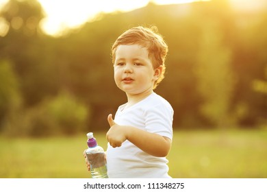 baby boy with brown hair drinking water in the park, holding plastic bottle and showing thumb up. outdoor shot