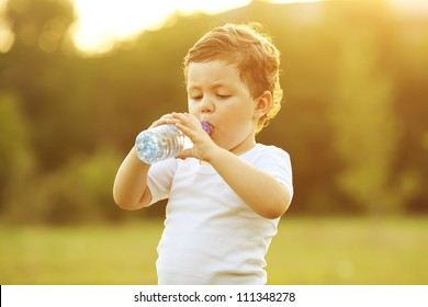 baby boy with brown hair drinking water in the park, holding plastic bottle. outdoor shot
