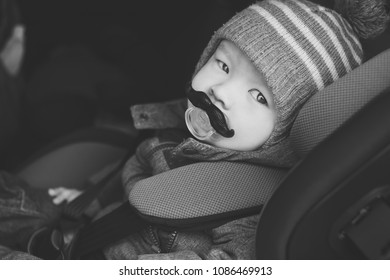 baby boy in car seat with funny dummy in mouth