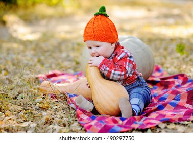 baby boy chewing on a pumpkin on a plaid blanket on a background autumn forest