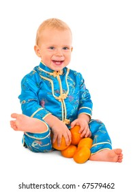 Baby boy in Chinese suit playing with mandarins