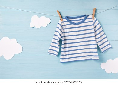 Baby boy clothes and cute white clouds on a clothesline, blue background