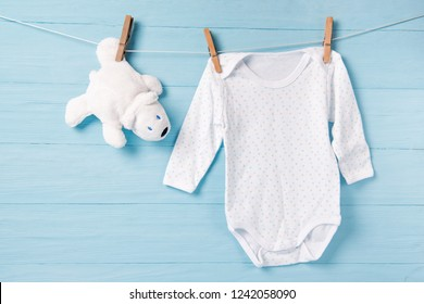 Baby boy clothes and white bear toy on a clothesline, blue background
