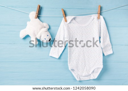 77171f1d9 Baby boy clothes and white bear toy on a clothesline, blue background