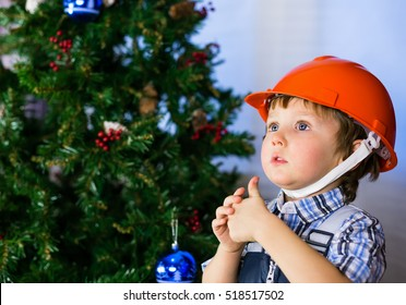 Baby boy in the construction helmet on a background of the Christmas tree showing thumb OK