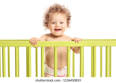 Baby boy in a cot bed looking at the camera and smiling isolated on white background