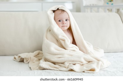 Baby boy covered in big towel after bathing