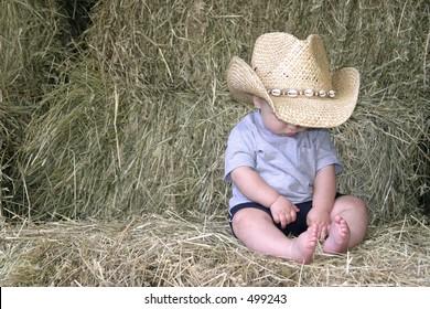 baby boy in cowboy hat sitting on hay bales