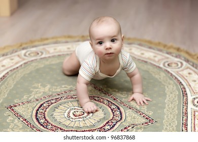 The baby boy crawling on a carpet at home
